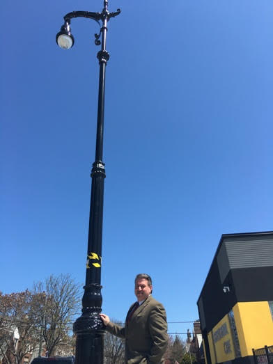 State Senator Joe Addabbo poses with one of the new decorative lamp posts in Glendale.